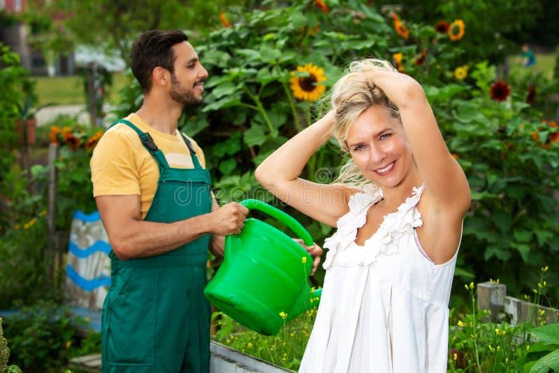 Paar in de tuin die de bloemen water geven stock fotografie