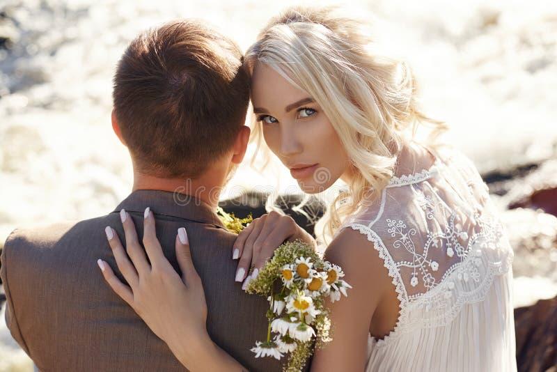 Paar in de zitting van het liefdeclose-up op een steen op een mooie Zonnige dag bij zonsondergang Liefdeemoties en omhelzingen in royalty-vrije stock foto's