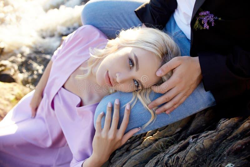Paar in de zitting van het liefdeclose-up op een steen op een mooie Zonnige dag bij zonsondergang Liefdeemoties en omhelzingen in royalty-vrije stock afbeelding