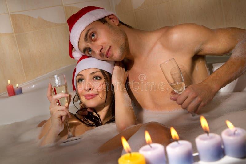 Paar in den Sankt-Hüten genießt ein Bad lizenzfreie stockbilder