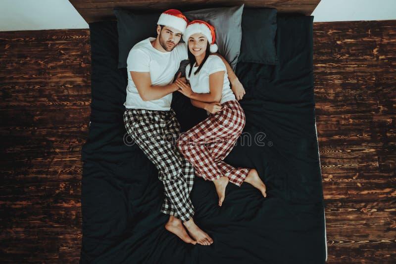 Paar in den Weihnachtshüten liegt auf Bett stockfotografie