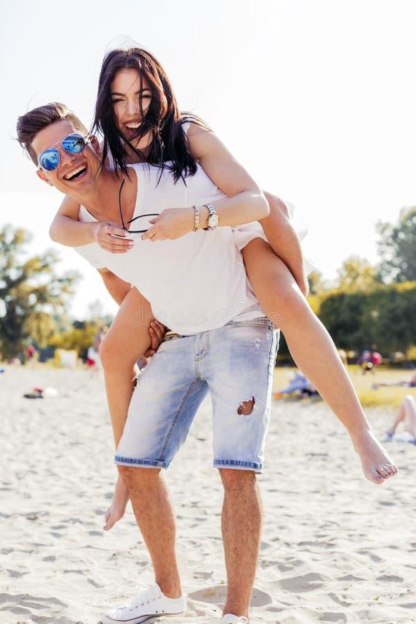 Paar in der Liebe, die ihre Sommerferien als der Mann genießt, trägt lizenzfreie stockfotos