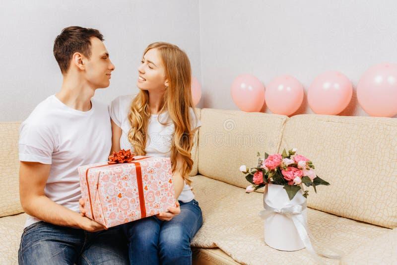 Paar in der Liebe, Mann gibt ein Geschenk, Frau sitzt zu Hause auf dem Sofa, Konzept des Tages der Frauen stockfotografie