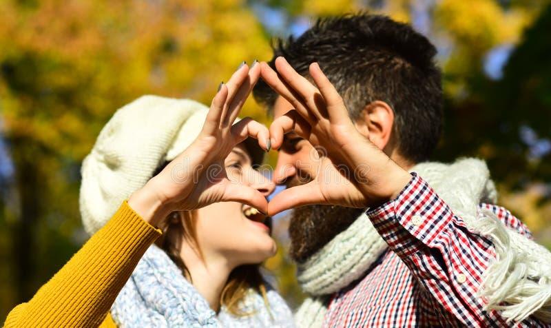 Paar in der Liebe mit Schals macht Herzzeichen mit den Fingern stockfotografie