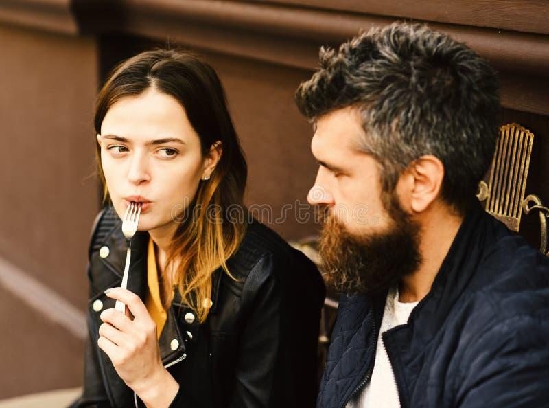Paar in der Liebe nimmt einen Biss während des Bruches Frau und Mann mit überraschten Gesichtern haben Datum am Café lizenzfreie stockbilder