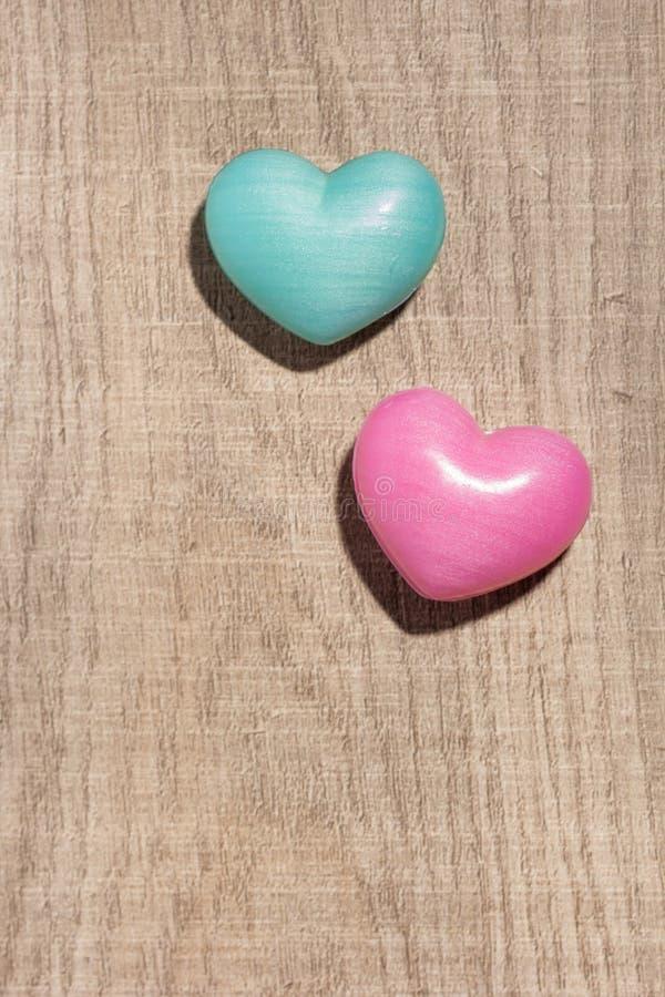 Paar des blauen und roten Herzens formt über Holztisch valentine lizenzfreie stockbilder