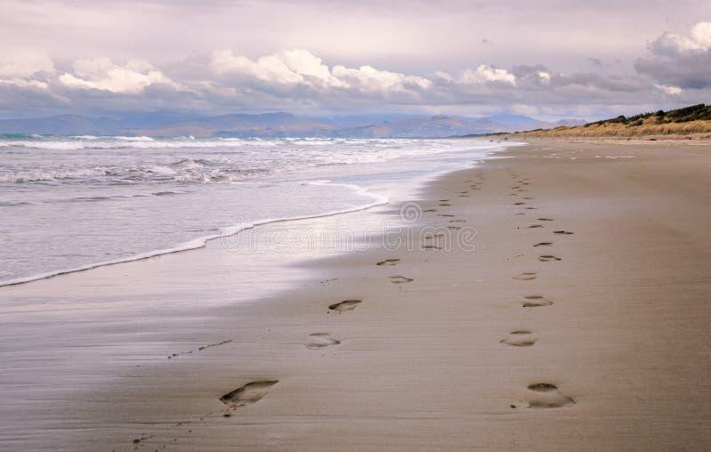 Paar des Fußes druckt auf einem einsamen Strand am bewölkten Abend stockbild