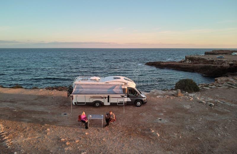 Paar dichtbij kampeerauto en mening aan de Middellandse Zee stock fotografie