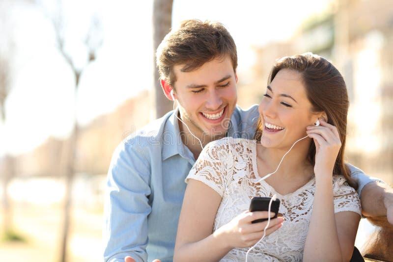 Paar die aan de muziek van een slimme telefoon luisteren royalty-vrije stock fotografie