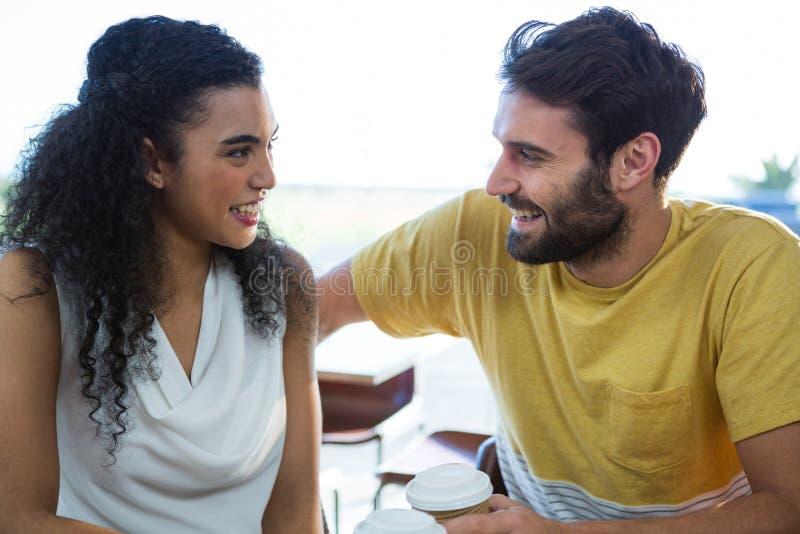 Paar die aan elkaar in koffiewinkel spreken royalty-vrije stock fotografie