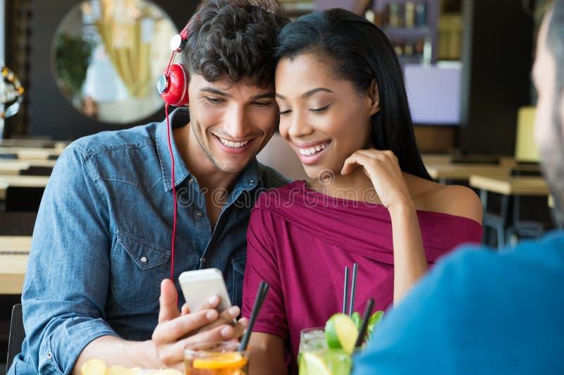 Paar die aan muziek bij bar luisteren stock afbeeldingen