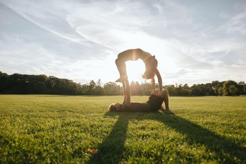 Paar die acrobatische yogaoefening doen bij park stock fotografie