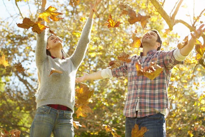 Paar die Autumn Leaves In The Air werpen royalty-vrije stock fotografie
