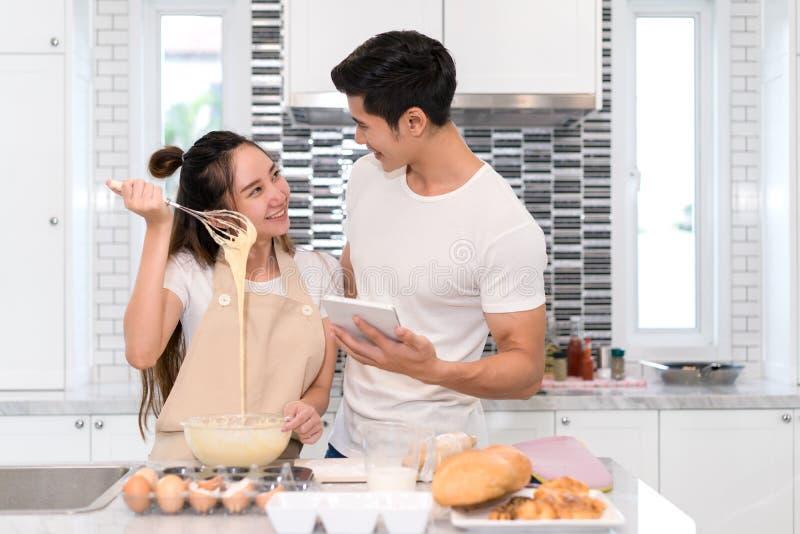 Paar die bakkerij, cake in keukenruimte, de Jonge Aziatische mens en vrouw samen maken royalty-vrije stock afbeeldingen