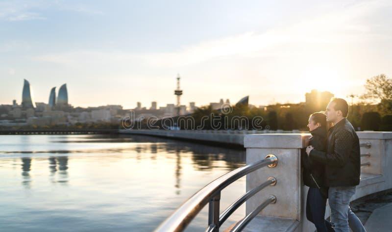 Paar die in Baku bij zonsondergang het overzees bekijken Mensen op een vakantieontsnapping Gelukkige man en vrouw op een datum Re stock afbeelding