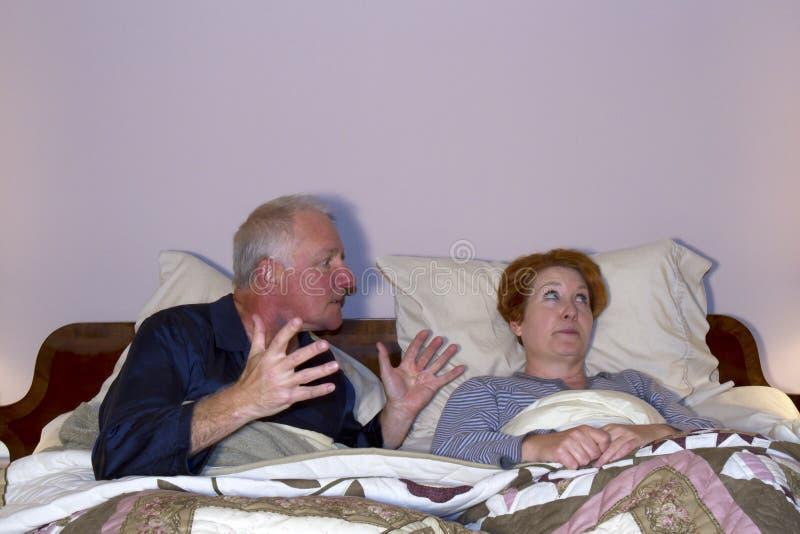 Paar die in Bed debatteren stock foto