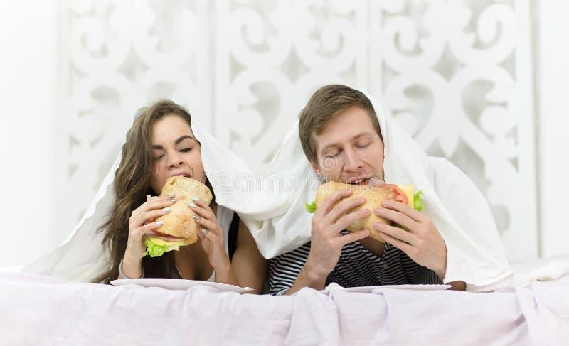 Paar die in bed eten stock afbeeldingen