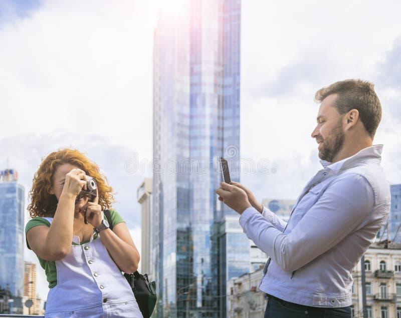 Paar die beeld nemen door smartphone en uitstekende camera Oud versus nieuw concept Dag, openlucht stock afbeelding