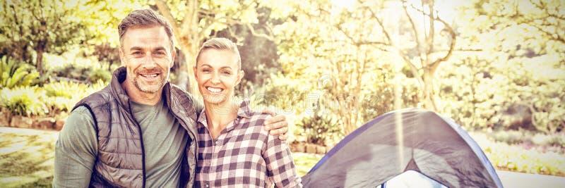 Paar die bij camera glimlachen terwijl jonge geitjes die in tent zitten royalty-vrije stock foto's