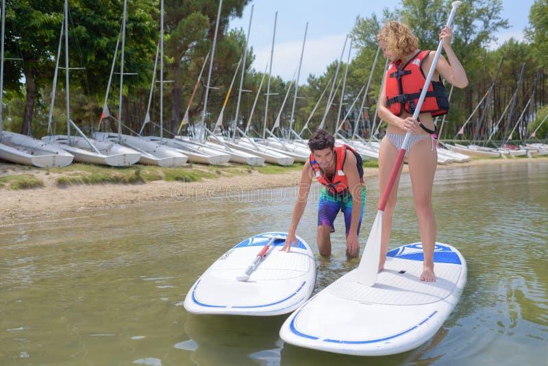 Paar die bij het windsurfing van raad vertrekken royalty-vrije stock fotografie