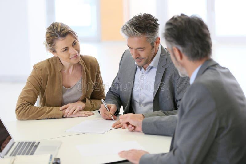 Paar die contract in bank ondertekenen royalty-vrije stock foto