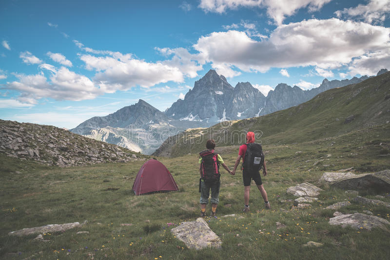 Paar die de majestueuze mening van gloeiende bergpieken bekijken bij zonsondergang hoog omhoog op de Alpen Achtermening met het k stock afbeelding