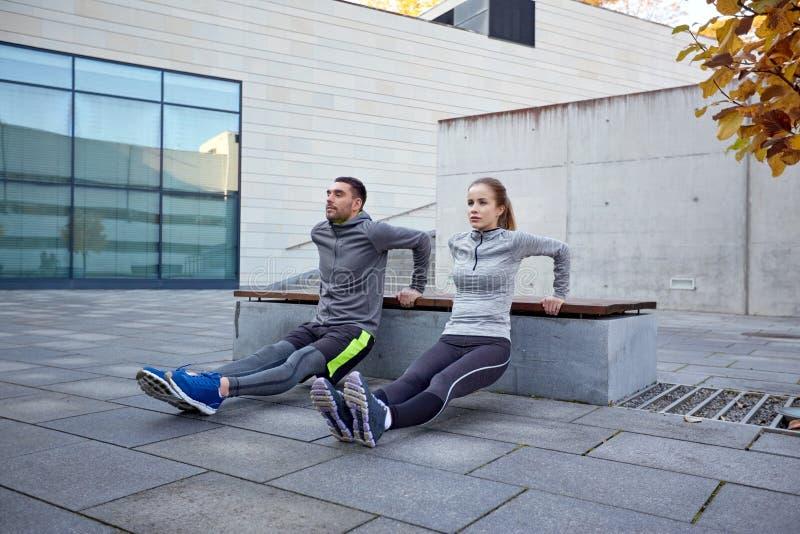 Paar die de oefening van de tricepsonderdompeling in openlucht doen stock afbeelding