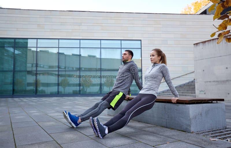 Paar die de oefening van de tricepsonderdompeling in openlucht doen stock fotografie