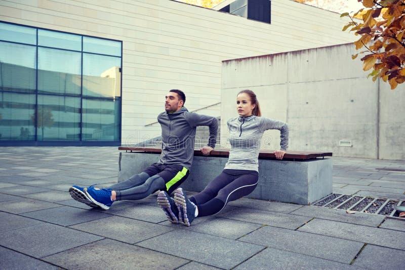 Paar die de oefening van de tricepsonderdompeling in openlucht doen royalty-vrije stock fotografie