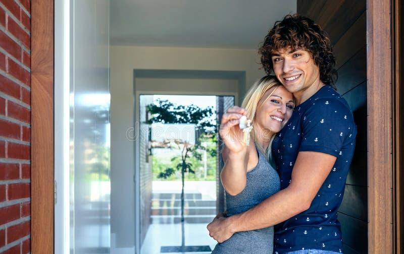 Paar die de sleutels van hun huis tonen stock afbeeldingen