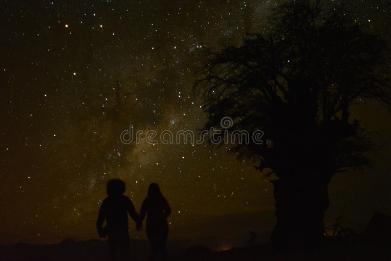 Paar die de sterren tijdens een mooie nacht in Atacama-woestijn bekijken stock foto's
