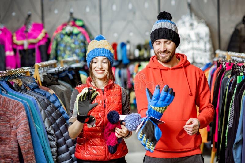 Paar die de winterkleren in de winkel proberen royalty-vrije stock afbeeldingen