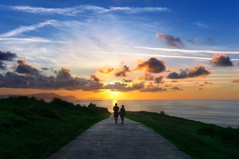 Paar die dichtbij overzees lopen stock foto's