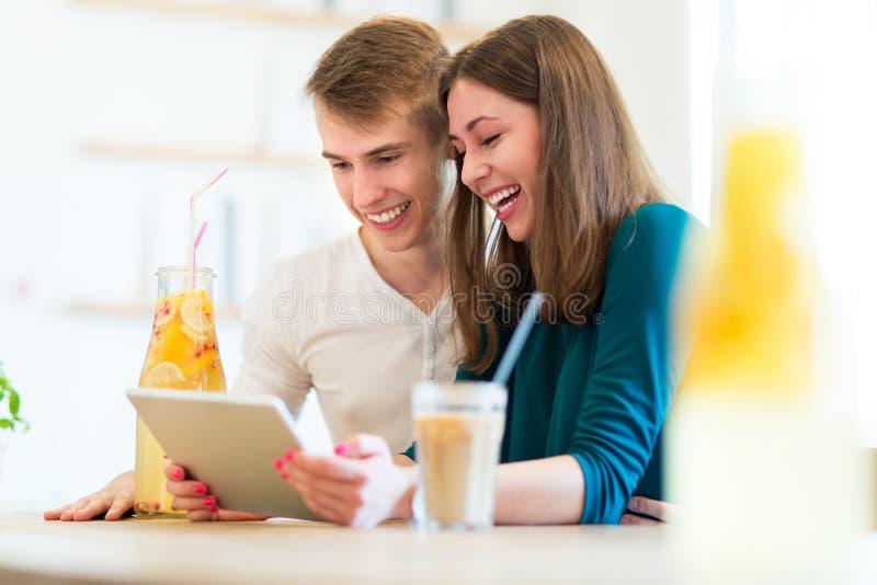 Paar die digitale tablet gebruiken bij koffie royalty-vrije stock afbeelding