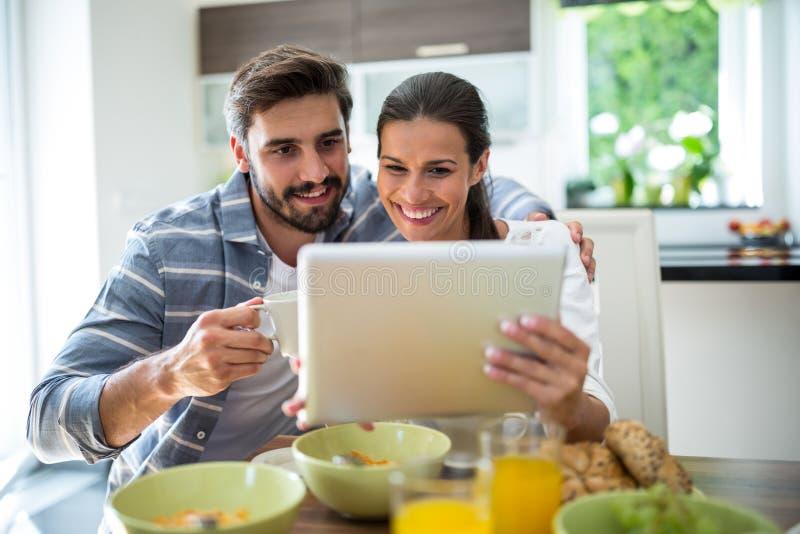 Paar die digitale tablet gebruiken terwijl het hebben van ontbijt royalty-vrije stock foto