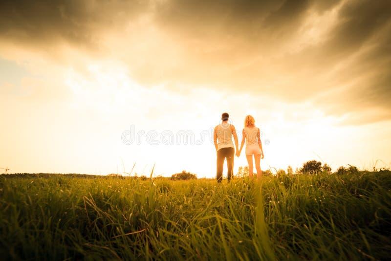 Paar die door het gebied lopen en handen houden royalty-vrije stock afbeelding