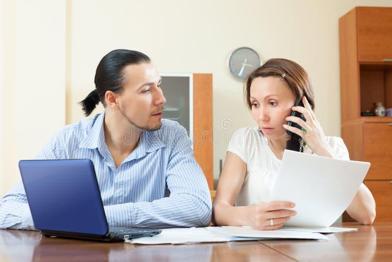 Paar die door mobiel over financiële documenten roepen royalty-vrije stock afbeeldingen