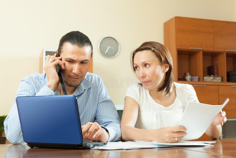 Paar die door mobiel over financiële documenten roepen stock foto's