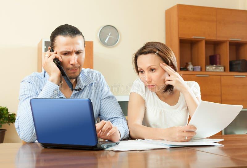 Paar die door mobiel over financiële documenten thuis roepen royalty-vrije stock foto