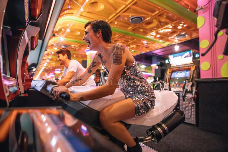 Paar die een arcade het rennen spelzitting op fietsen spelen royalty-vrije stock afbeelding