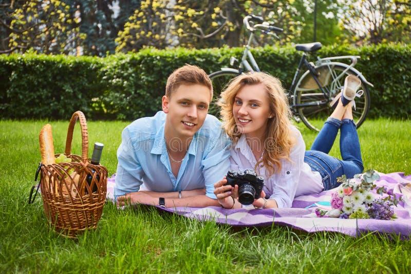 Paar die een compacte fotocamera met behulp van bij een picknick royalty-vrije stock afbeelding