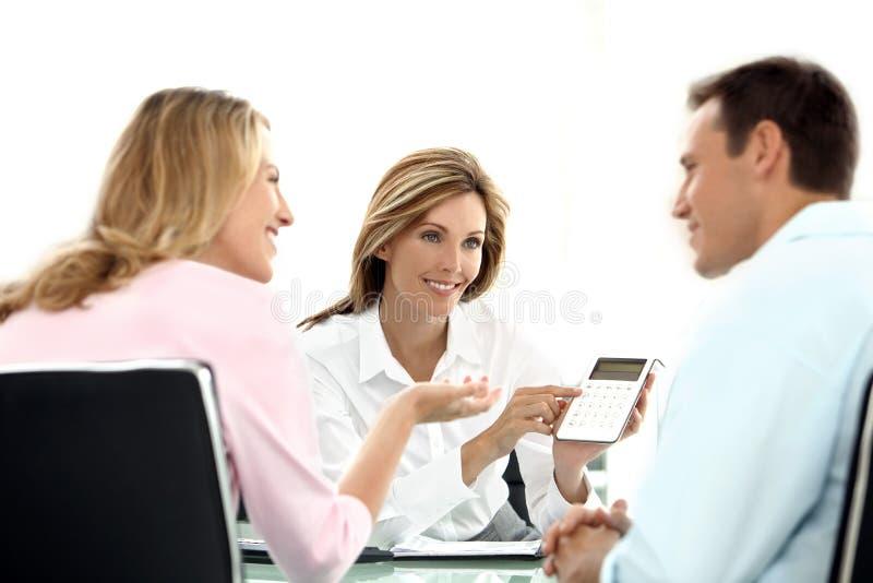 Paar die een financiële adviseur behandelen bij de bank stock foto