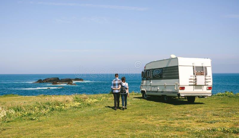 Paar die een gang nemen dichtbij de kust met een kampeerauto royalty-vrije stock foto's