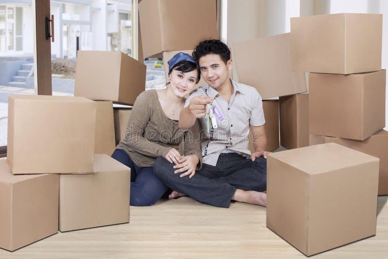 Paar die een huissleutel binnenshuis tonen stock fotografie