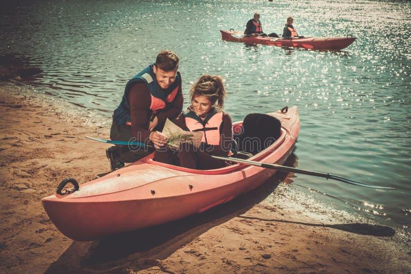 Paar die een kaart in kajaks op een strand lezen stock foto