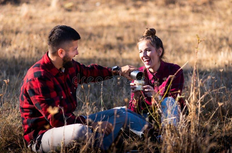 Paar die een kop van koffie op een picknick delen royalty-vrije stock fotografie