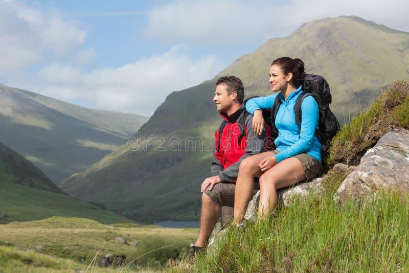 Paar die een onderbreking na bergop wandeling nemen royalty-vrije stock fotografie
