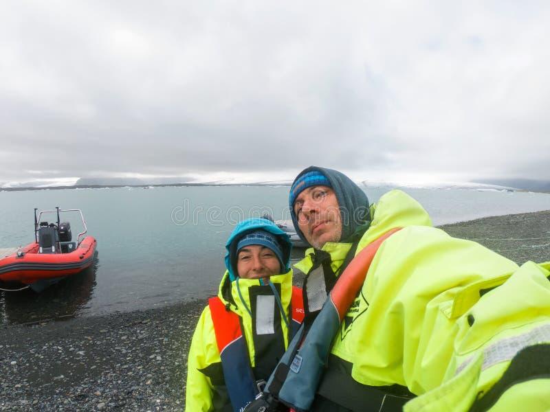 Paar die een selfie in de kleren van de veiligheidsinflatie in Jokulsarlon, IJsland maken royalty-vrije stock foto