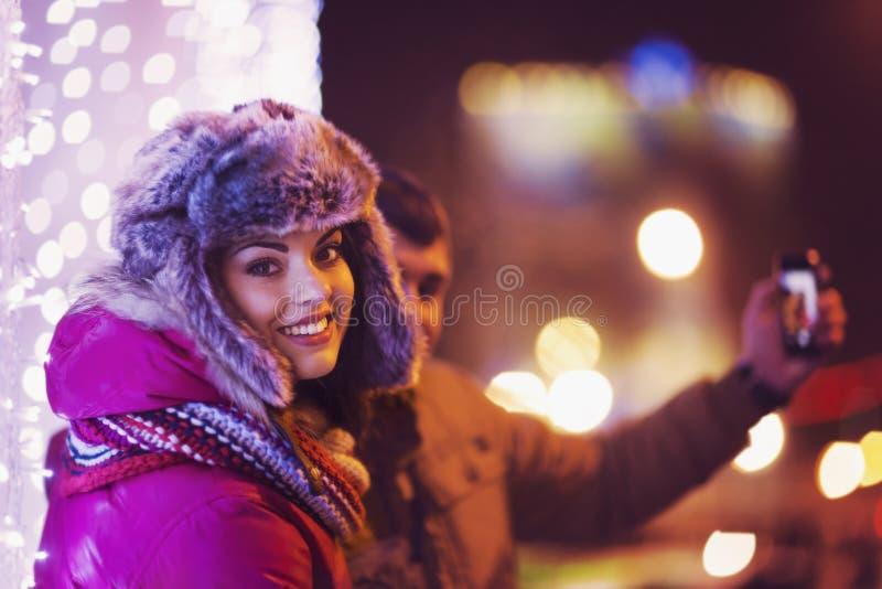 Paar die een selfie met een Kerstmisboom maken bij achtergrond stock afbeeldingen