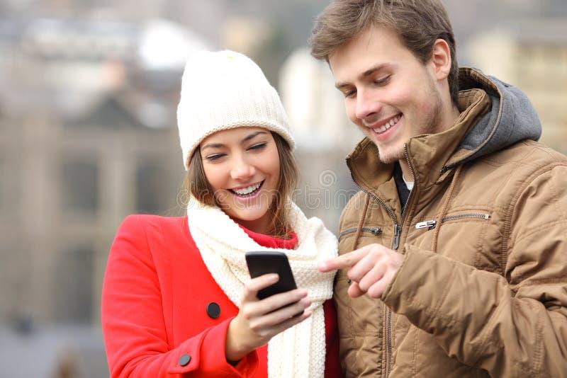 Paar die een slimme telefoon in de winter raadplegen stock foto